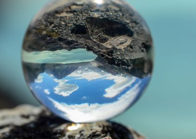 Crystal ball on a black stone mirroring the image of a lake with mountains