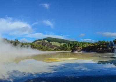 Panoramic view of geothermal pools with smoke going out from blue and green water