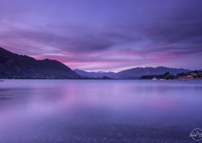 Lake after sunset with water and sky in blue and purple hue, mountains in the horizon, water seems frozen