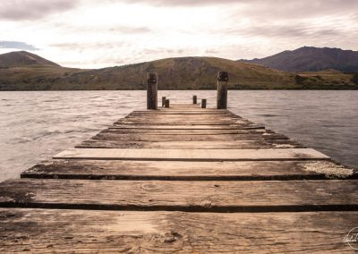 Wooden dock facing a lake with mountain in the background